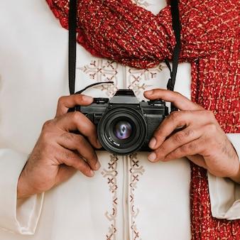 Uomo indiano in un kurta con una fotocamera digitale