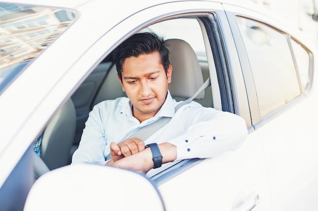 Uomo indiano che guarda un orologio intelligente mentre è seduto in macchina