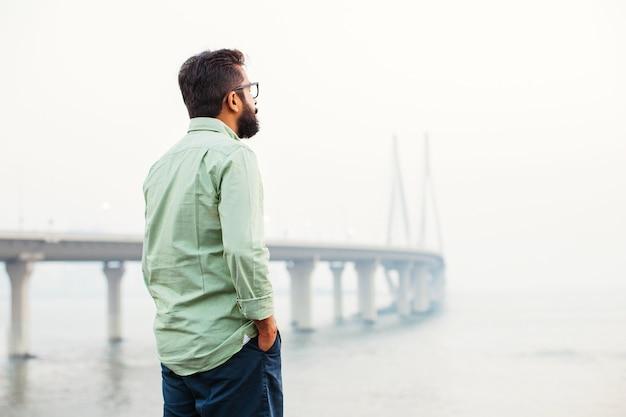 Uomo indiano in piedi e pensando davanti al ponte a mumbai