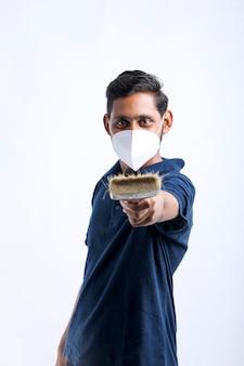Uomo indiano che utilizza un martello per il salvadanaio rotto dell'argilla.