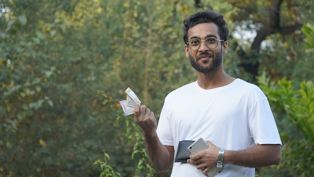 Uomo indiano con denaro contante online sul telefono cellulare,