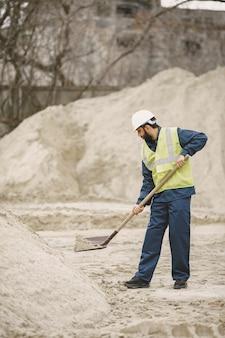 Uomo indiano che lavora. maschio in una maglia gialla. uomo con una pala /