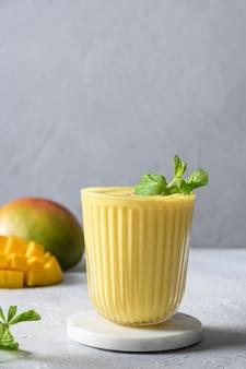 Mango indiano o lassi alla curcuma su sfondo grigio
