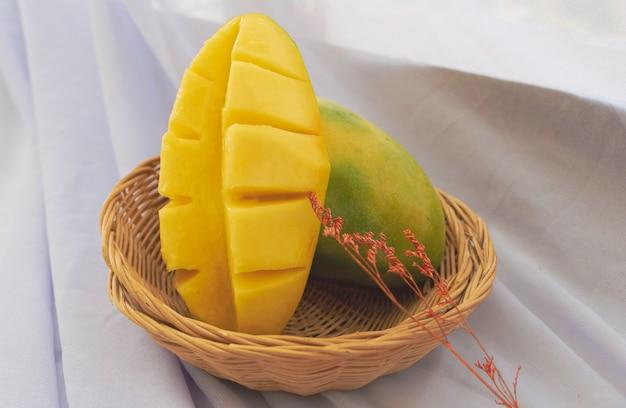 Mango indiano con polpa gialla messo in un cesto intrecciato, sullo sfondo