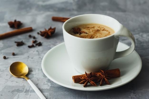Indiano tè masala chai tè speziato con latte su sfondo grigio cemento
