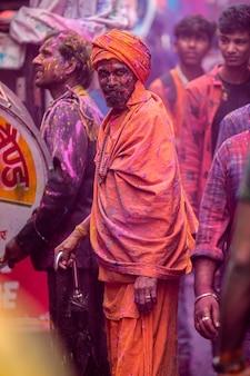 Uomini indiani che si godono l'holi festival con i colori della folla