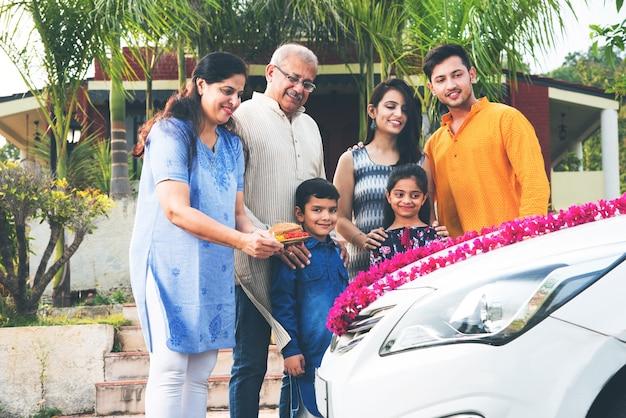 Genitori indiani moderni con bambini che accolgono tradizionalmente il nuovo ca, eseguendo pooja