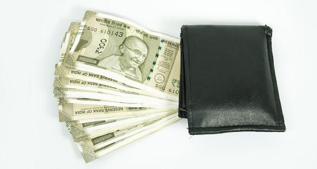 Soldi indiani con portafoglio isolare in superficie bianca