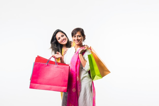 Indian madre figlia sorelle shopping con borse colorate, in piedi isolato su sfondo bianco