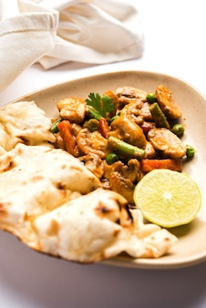 Curry di funghi indiani o masala di funghi secchi semy con roti o naan o pane piatto, fuoco selettivo