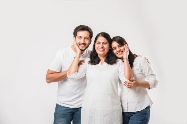 Vecchia madre indiana imbarazzante per i giovani adulti. famiglia asiatica di 3 persone in piedi isolato su sfondo bianco. messa a fuoco selettiva