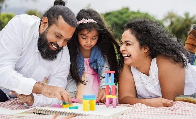 Genitori indiani che si divertono al parco cittadino a giocare con i giocattoli di legno con la figlia