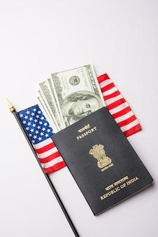 Passaporto indiano con dollari usa con bandiera americana sullo sfondo, concetto che mostra la richiesta di visto turistico o h-1b