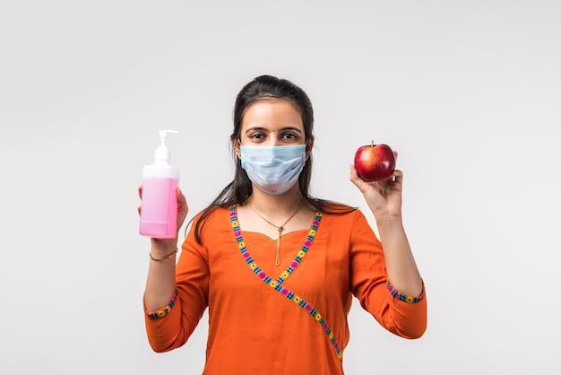 La bella ragazza indiana indossa la maschera per il viso igienizzante la mela o applica il disinfettante sulla frutta