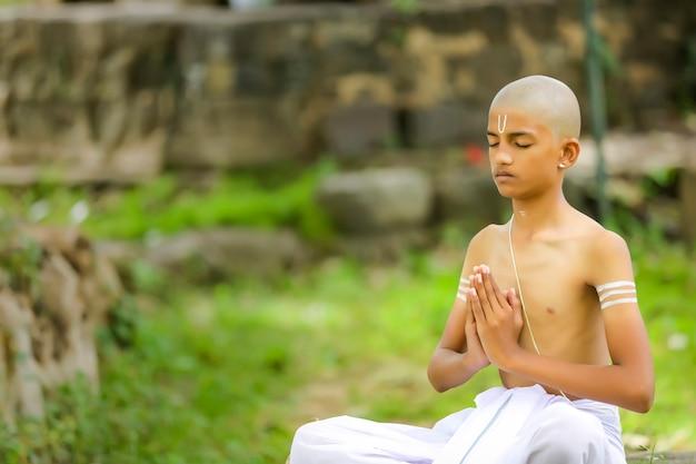 Il bambino sacerdote indiano che fa meditazione