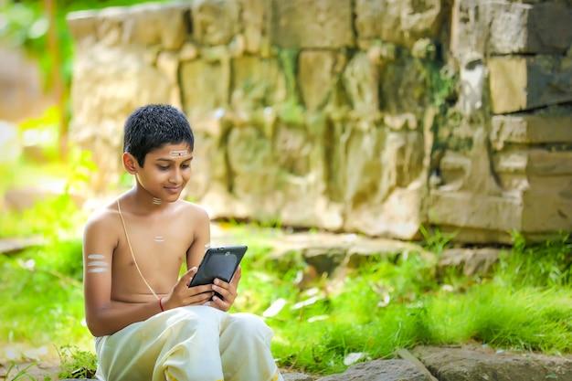 Il bambino sacerdote indiano utilizza lo smartphone