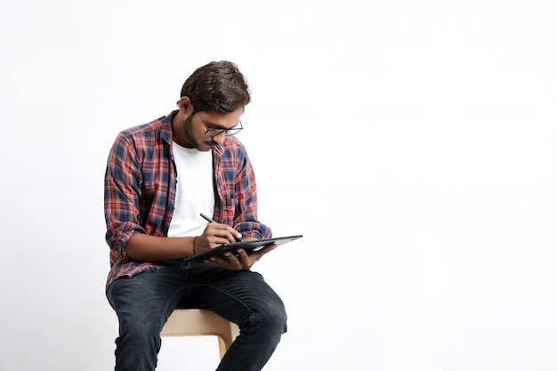 Designer professionista indiano utilizzando tavoletta grafica collegata allo smartphone con penna digitale