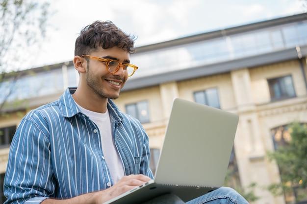Programmatore indiano che utilizza laptop, internet, progetto di lavoro freelance online, seduto nel parco