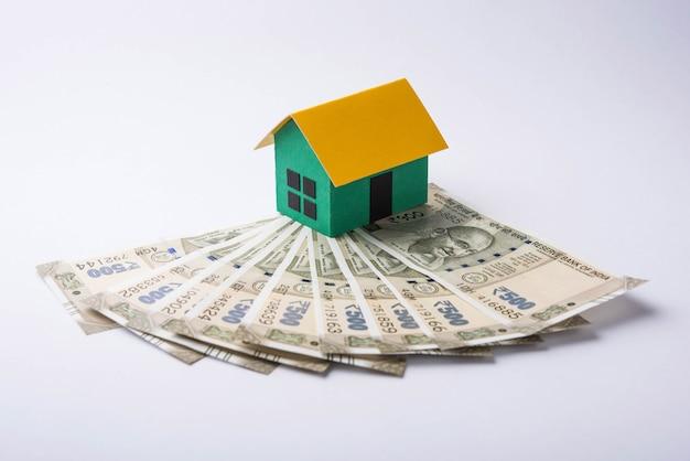 Concetto di business immobiliare indiano che mostra casa modello 3d con chiavi, banconote in valuta cartacea e calcolatrice. messa a fuoco selettiva