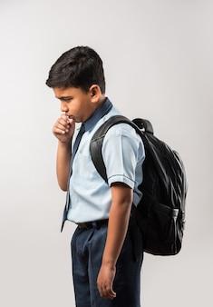 Indian school boy tosse mentre indossa uniformi scolastiche e zainetto, isolato su sfondo bianco