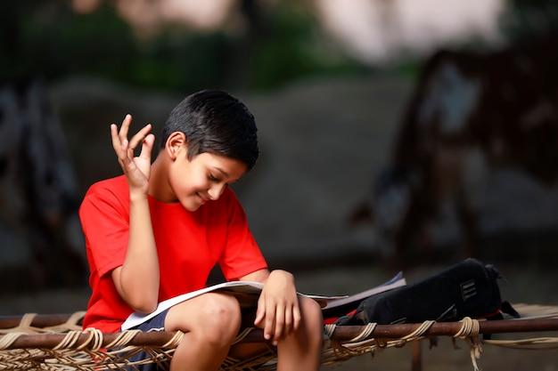 Ragazzo di scuola indiano con taccuino e studiare a casa