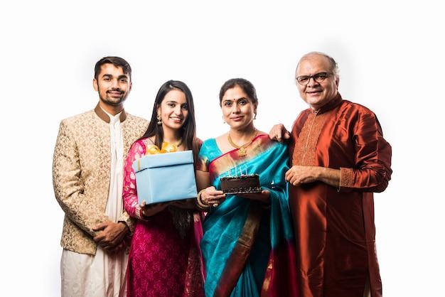 Donna anziana indiana con la famiglia che festeggia il compleanno soffiando candele sulla torta mentre indossa abbigliamento etnico