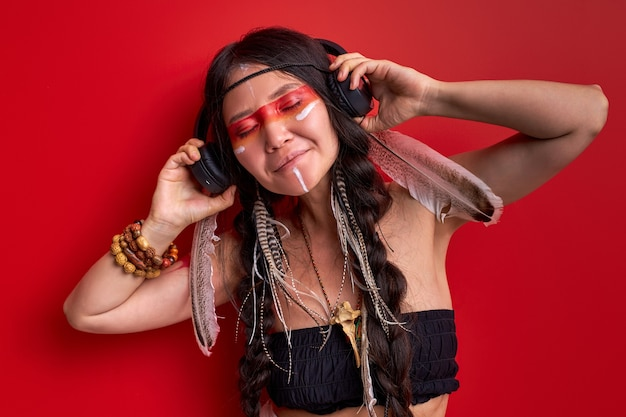Donna sciamano indiana che ascolta la musica in cuffie senza fili, godendo delle moderne tecnologie