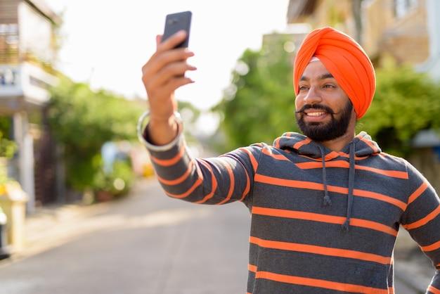 Uomo indiano sikh che indossa turbante e prendendo selfie con il telefono