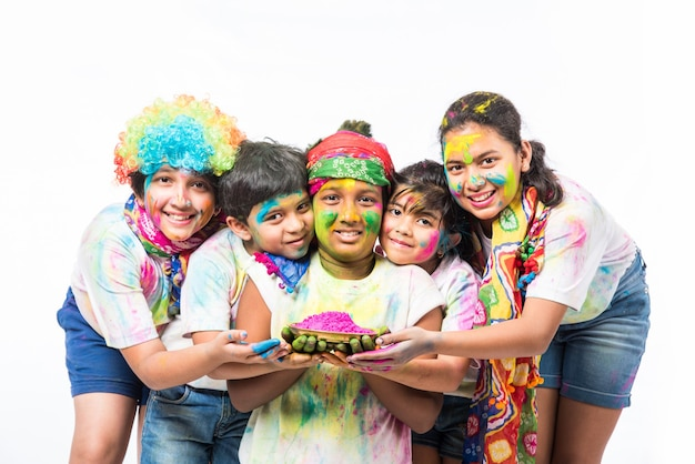 Bambini piccoli indiani o amici o fratelli che celebrano il festival di holi con gulal o color polvere, dolci, pichkari o spray, isolati su sfondo bianco