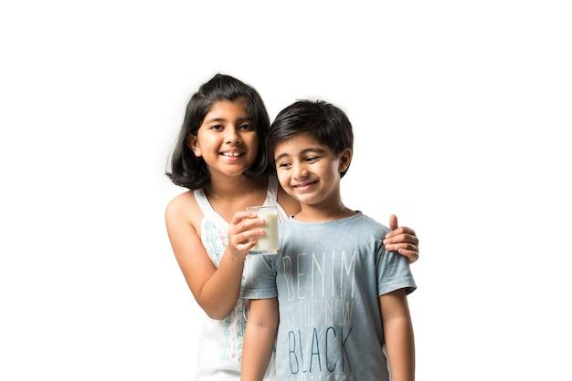 Piccoli fratelli o amici indiani che tengono o hanno un bicchiere pieno di latte contro il muro bianco