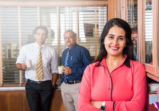 Donna d'affari indiana intelligente in piedi con le braccia conserte mentre altri 2 uomini d'affari bevono caffè e discutono in sottofondo