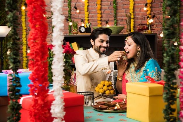 Coppia intelligente indiana che mangia laddu dolce il diwali o l'anniversario, messa a fuoco selettiva