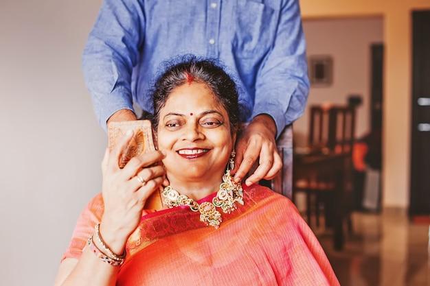 Figlio indiano che mette gioielli a sua madre