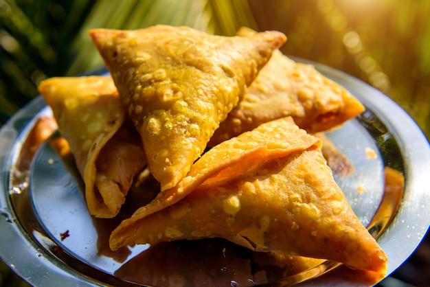 Samosa snack farciti indiano su piastra metallica