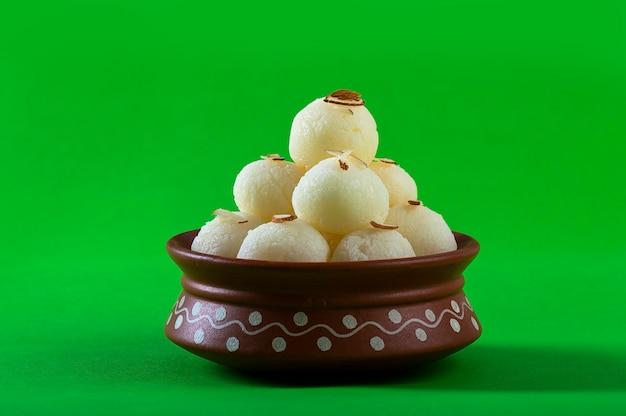 Dolce o dessert indiano - rasgulla, famoso dolce bengalese in una ciotola di argilla su sfondo verde