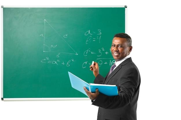 Insegnante indiano che spiega le formule matematiche scritte sulla lavagna