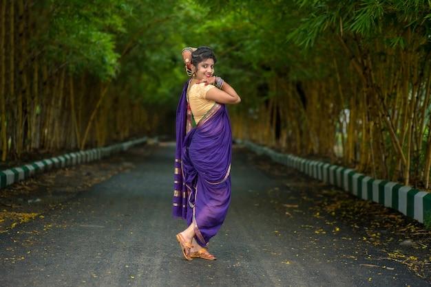 Indiana tradizionale bella ragazza in saree in posa all'aperto