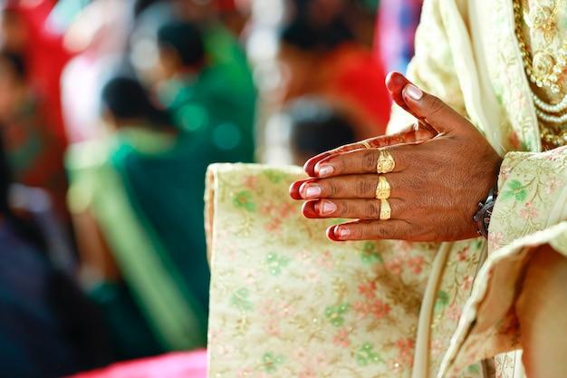 Matrimonio tradizionale indiano: anello d'oro nella mano dello sposo