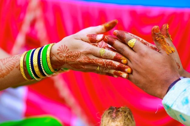 Matrimonio tradizionale indiano sposo mano nella cerimonia haldi
