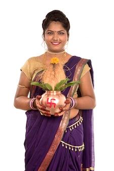 Donna tradizionale indiana che tiene un kalash di rame tradizionale, festival indiano, kalash di rame con cocco e foglia di mango con decorazione floreale, essenziale nella puja indù.