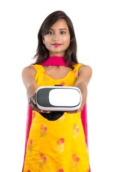 Giovane ragazza tradizionale indiana che tiene e che mostra il dispositivo di vr, la scatola del vr, gli occhiali di protezione, la cuffia avricolare di vetro di realtà virtuale 3d, ragazza con l'imaging moderno la tecnologia futura su fondo bianco.