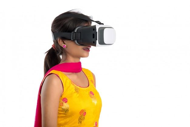 Ragazza tradizionale indiana che tiene e che mostra il dispositivo vr, scatola vr, occhiali, cuffie per occhiali 3d di realtà virtuale