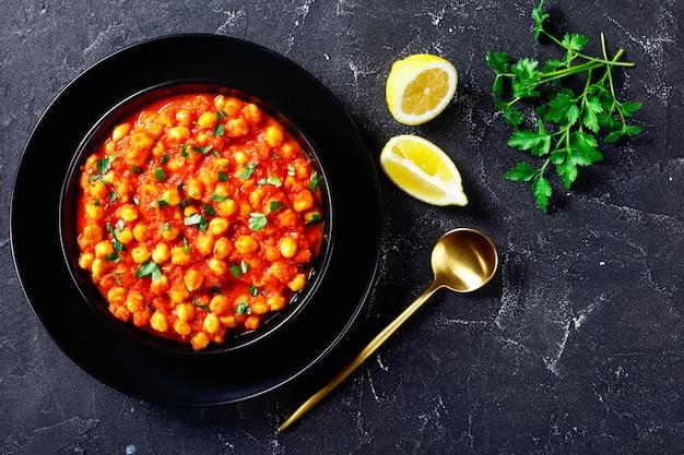 Piatto vegano indiano chana masala o curry di ceci con spezie, salsa di pomodoro cosparsa di prezzemolo su una piastra nera