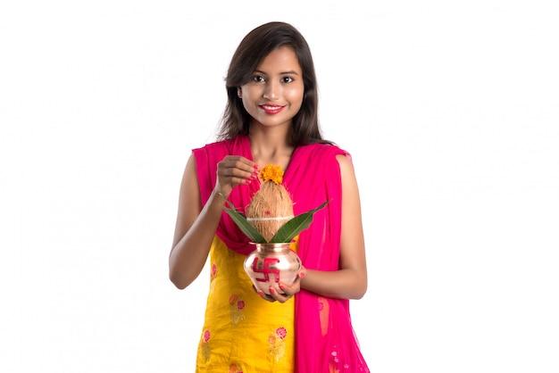 Donna indiana in possesso di un tradizionale kalash in rame, festival indiano, kalash in rame con foglie di cocco e mango con decorazioni floreali, essenziale in hindu pooja.