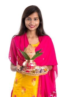 Donna indiana in possesso di un tradizionale kalash in rame con pooja thali, festival indiano, kalash in rame con cocco e foglia di mango con decorazioni floreali, essenziale in hindu pooja.