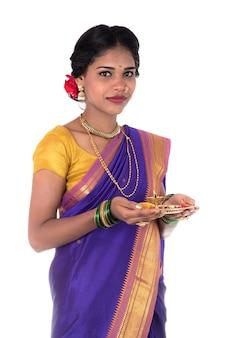 Donna indiana che esegue il culto, ritratto di una giovane e bella donna con pooja thali isolato su sfondo bianco