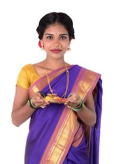 Culto di esecuzione della donna indiana, ritratto di bella giovane signora con il thali di pooja isolato sulla parete bianca