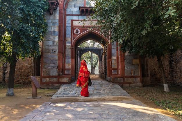 Donna indiana in sari rosso vicino arab ki sarai gateway della tomba di humayun, new dehli, india.