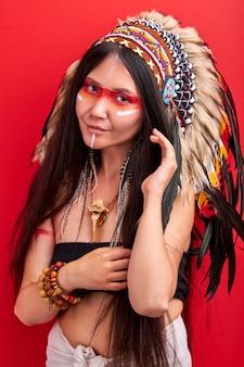 Donna indiana in costume sciamanico in posa, con un sorriso timido