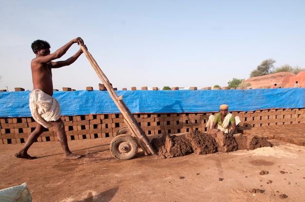 Lavoratori indiani che producono mattoni tradizionali a mano nella fabbrica di mattoni